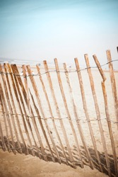 wooden fence at the beach with blue sky