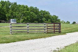Wooden fence by a gravel lane