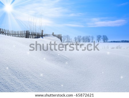 Wooden fence covered with snow under blue sky sunny day - stock photo