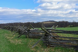 wooden fence , field, and big round top mountain  near cemetery ridge in the historical gettysburg battlefield,  pennsylvania