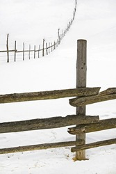 wooden fence for animals on a hill in winter