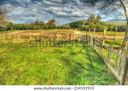 wooden fence in a green field. Processed for hdr tone mapping effect.