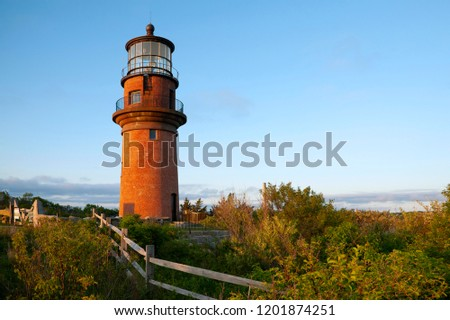 Wooden fence leads to the large brick tower of Aquinnah lighthouse, also referred to as Gay Head light, on a late summer day on Martha's Vineyard island in Massachusetts. #1201874251
