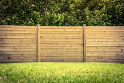 Wooden fence on a green lawn