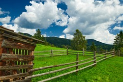 wooden fence on a ranch closeup, beautiful summer landscape, spruces on hills, cloudy sky and wildflowers - travel destination scenic, carpathian mountains