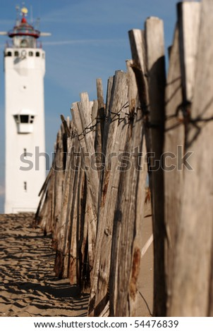 Wooden fence on out of focus lighthouse background. North sea, Noordwijk.
