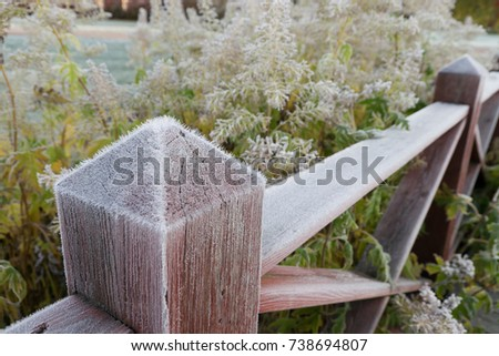 Wooden fence post covered with hoar frost on an cold autumn morning. #738694807
