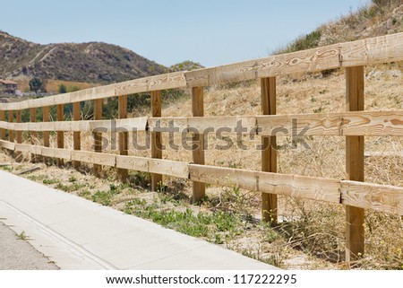 Wooden fence runs along a street in a rural area.