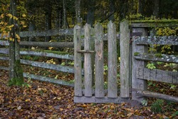 Wooden fence with a half-open gate.