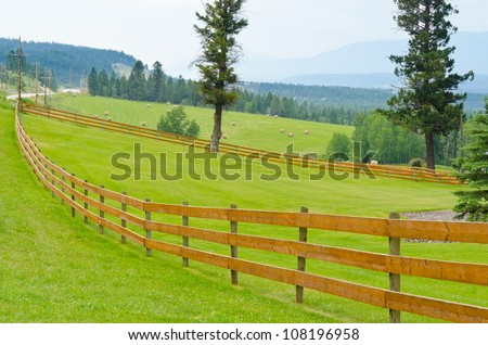 wooden fence with green field and rolled hay