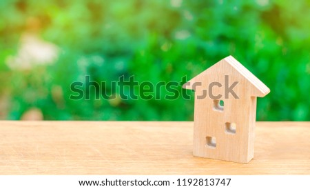 Wooden figure of a multi-storey house on a green background. Three-story house. Buying and selling of real estate, construction. Apartments and apartments. Minimalism. for presentations.