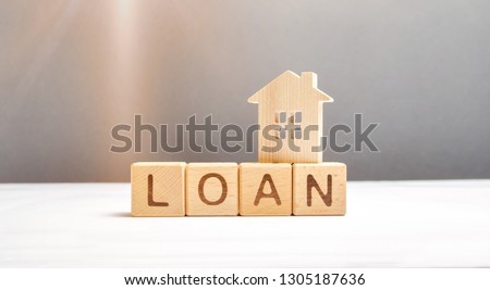 Wooden figure of the house and the cubes with the inscription loan. Mortgage programs and the purchase of affordable housing for young families and citizens. Maintain a demographic increase.