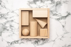 Wooden figures in box on marble background. Abstract background of wooden objects. Geometric composition. Scene with geometrical forms top view