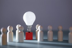 Wooden figures, lightbulb on red cube. Team creativity, idea mockup. Creative approach and lateral thinking, copy space