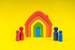 Wooden figures, miniature people standing in front of rainbow color house on yellow background. Divorce, conflict between parents, children custody after divorce