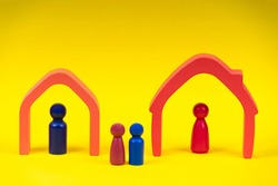 Wooden figures, miniature people standing inside of houses and children between them on yellow background. Divorce, conflict between parents, children custody after divorce.
