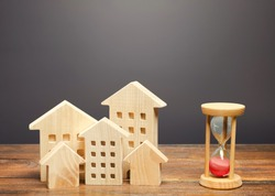 Wooden figures of houses and sand hourglass. Mortgage and loan concept. Temporary rental housing and residence permit. Time to pay taxes and bills. Realtor services for a quick search for options.