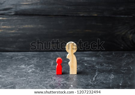 Wooden figures of mother and red child. The concept of maturation and self-reliance. Under the wing of the mother. Child education. The baby is separated from the mothers body.