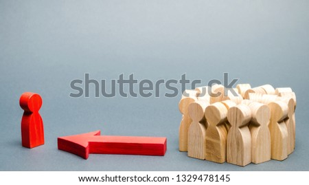 Wooden figures of people. The boss of the business team indicates the direction of movement to the goal. The crowd is following the leader. The concept of leadership and team management. Teamwork. #1329478145