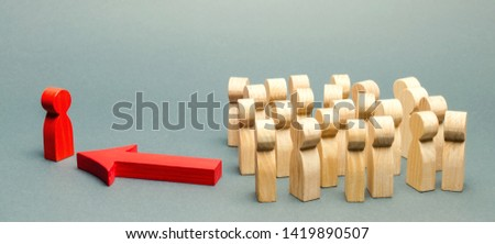 Wooden figures of people. The boss of the business team indicates the direction of movement to the goal. The crowd is following the leader. The concept of leadership and team management #1419890507