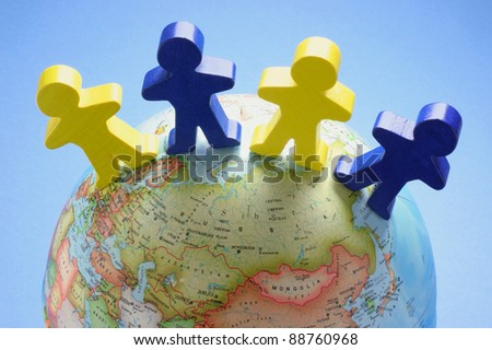 Wooden Figures on Globe with Blue Background