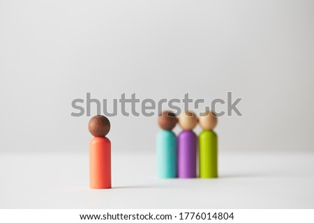 Wooden figurines concept. One person standing in front of a group of people, separated and with focus on one person. Chosen one, speaking. Highlighted. Kids wooden toys. Stock photo ©