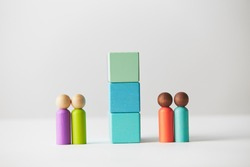 Wooden figurines concept. Two wooden figurine couples standing separated by a wall of blocks. Black and white skin colour. Racial and social issues. Kids toys