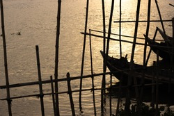 Wooden fishing boat bounded with the dark bamboo fence in the sunset evening on the river