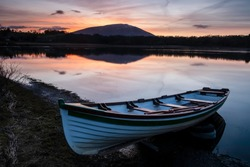 Wooden fishing boat moored in foreground still water lake and Nephin mountain in Background with orange red sky reflected in water.