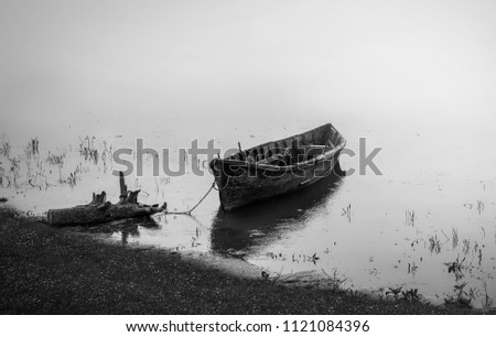 Wooden fishing boat on water.Black and white photography