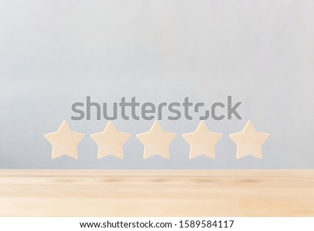 Wooden five star shape on table. The best excellent business services rating customer experience concept