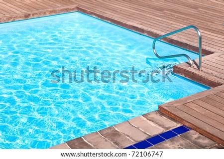 Wooden floor beside the blue swimming pool