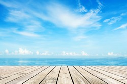 Wooden floor with blue sea and sky background