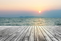 Wooden floor with blur sea at sunset