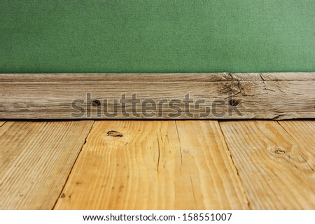 wooden floor with old green wall