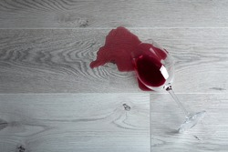 Wooden floor with overturned glass of red wine. Spilled wine on a wooden laminate (parquet) floor with moisture protection.