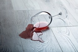 Wooden floor with overturned glass of red wine. Spilled wine on a wooden laminate (parquet) floor with moisture protection. Concept of alcoholism, broken relationships, depression
