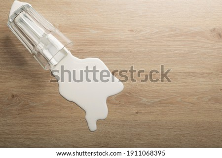 Wooden floor with overturned glass of white milk. Spilled  white milk on a wooden laminate (parquet) floor with moisture protection. Foto stock ©