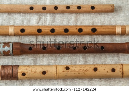 Wooden flute on grey linen tablecloth #1127142224