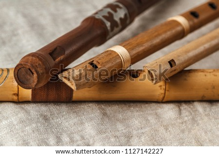 Wooden flute on grey linen tablecloth #1127142227