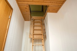 Wooden folding ladder to the attic, old empty house close-up