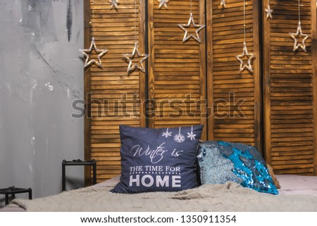 Wooden folding screen for interior. Bed on wooden folding screen background. Decorative element. Colorful pillows on the bed. #1350911354