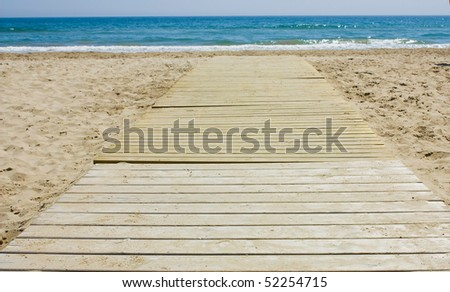 Wooden footbridge in the sand of a beach for access to the sea