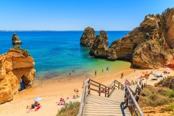 Wooden footbridge to beautiful beach Praia do Camilo, Portugal