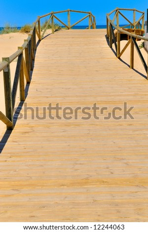 wooden footbridge towards the beach - stock photo