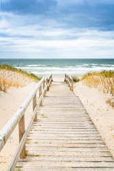 Wooden footpath on dune on Sylt. Entrance for the beach. North Germany.