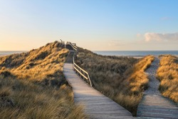 Wooden  footpath through the dunes to the beach of Norddorf on German North Sea island Amrum, late afternoon
