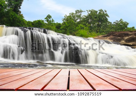 Wooden foreground with blurred Waterfall background, Old wooden foreground with blurred Waterfall background, empty space Place a product. Nature and health concept  #1092875519