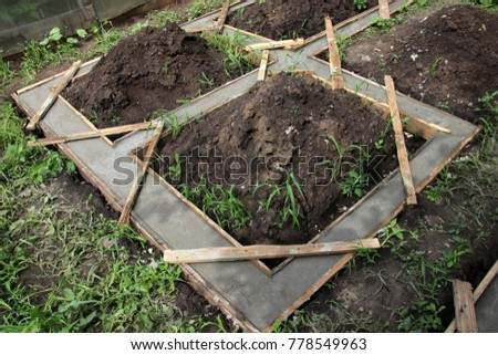 Wooden formwork concrete strip foundation for raised flower beds in the summer garden Stock photo ©