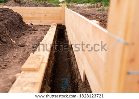 Wooden formwork for creating strip foundation for new house basis. Constructing house from the beginning concept Stock photo ©